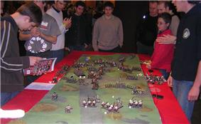 Several men surround a table, on which lies a small scale model of an undulating ground.  Many small figures of monsters and medieval warriors and siege weapons are placed on that terrain.  Dice are scattered among the figures.