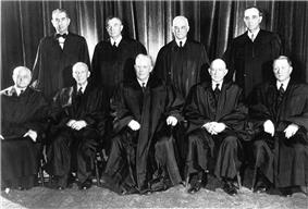 Five men sitting in a row with four men standing behind them. All wear flowing back robes and a large black curtain is behind them