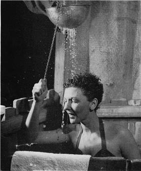 Martin, wearing a swimsuit, stands in an improvised shower stall as water pours down on her.