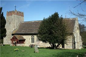 A mainly stone church seen from the south showing a tower with a battlemented brick parapet, a porch, and a roof with red and black tiles in bands