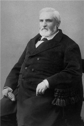 Back and white photo of a man wearing a suit sits on a chair