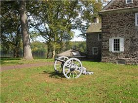 Photo shows an 18th-century cannon, probably a 3-pounder, with an old stone building and the Delaware River in the background.