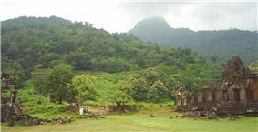 Ruins of stone buildings in a very green lush mountain landscape.