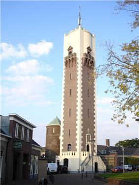 A water tower standing in the middle of several small, end 19th-century houses