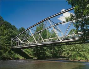 A metal-frame bridge over a broad stream in a forest