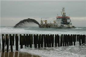 A ship sailing just in front of the beach. From the ship a dark jet of sand and water is blown towards the coast