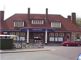 A brown-bricked building with a red-tiled roof and a rectangular, dark blue sign reading