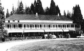 Historic photograph of the Wawona Hotel, a broad, two-story building with trees in the background.