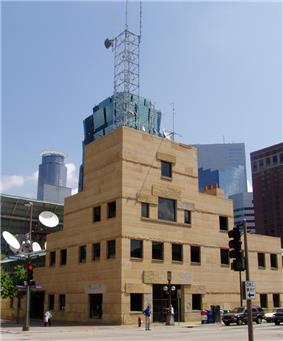 sandstone tower with square windows on the corner of the Nicollet Mall