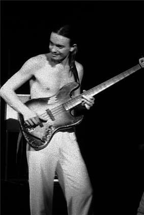 Pastorius, shirtless, playing bass in his early years.