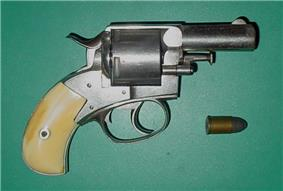 Snub-nosed revolver with yellow handle and its bullet