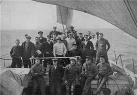 A group of men on board a ship, identified by a caption as