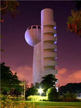A night-time image of a gray windowless tower, with an egg-shaped windowed observation deck on top. Next to it is a low building, grass, and many trees and bushes.