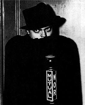 Man in black hat concealing the bottom of his face with a black cape and gazing fiercely. A microphone in front bears the word