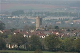 Roofs of several houses with the square tower of the church prominent amongst them. In the background are fields and hills.