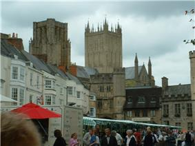 People at coloured market stalls. Surrounding are houses with the towers of the cathedral visible behind.