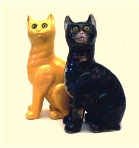 A black ceramic cat sits next to a yellow ceramic cat.