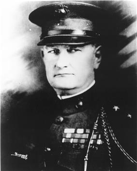 A black and white image of Wendell C. Neville, a white male in his Marine Corps dress blue uniform. He is wearing a hat and his French Fourragère can be seen, in addition to several ribbons.