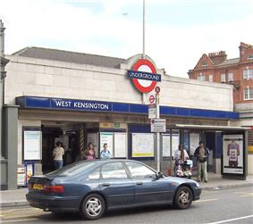 A white-bricked building with a rectangular, dark blue sign reading