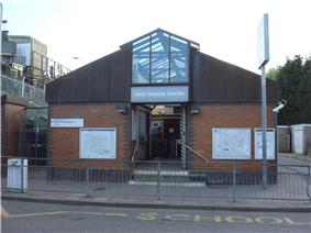 A brown-bricked building with a rectangular, light blue sign reading
