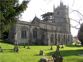 Gray stone building with arched windows and square tower. Foreground is grass with gravestones.