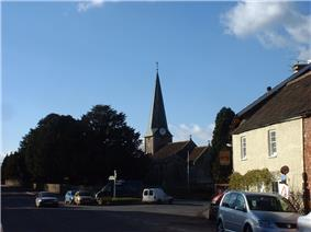 Street scene with a church and spire central to the picture. To the right is a yellow building with a pub sign. To the left is a large tree with a signpost in front. Several cars.