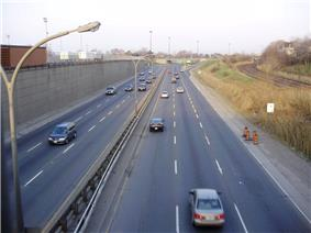 an 8-lane roadway from an overhead bridge with three parallel train tracks on the right