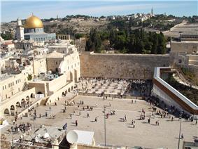 A large open area with people bounded by old stone walls. To the left is a mosque with large golden dome.