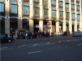 A large crowd of people walking on a grey sidewalk next to a black road where two vehicles are driving from the left to the right