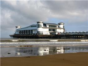 A walkway supported by metal legs arising from the sea, at the end of which is a large a white building with a wave-shaped roof and corner turrets.
