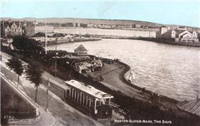 An old photograph of a tram running along a waterfront road.