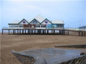 Building on stilts above sand.
