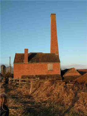 Red brick building with tall chimney.