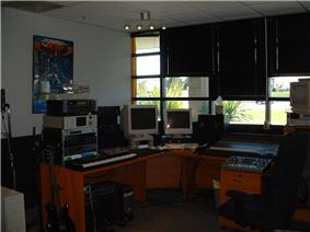 A musician's office with a solid wall and a wall containing windows shown, a microphone stand, an electric guitar, a mixing board, a keyboard, two computer monitors and a computer, a poster of the Transformers franchise