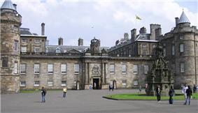 View of the Palace of Holyrood House showing the Royal Banner of Scotland flying from the rooftop flagpole, indicating that Her Majesty the Queen is not in residence.