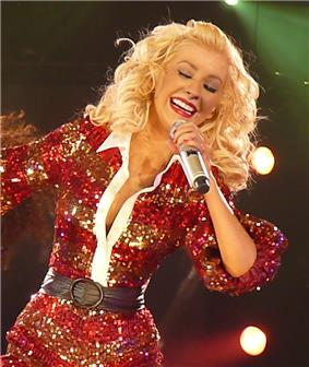 Aguilera wearing a red outfit performing with a microphone and smiling