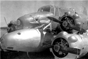 Two military monoplanes lying wheels down on a field, one atop the other