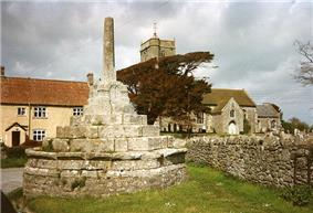 Stone steps up to a stone shaft which would once have had a cross at the top. To the left are yellow painted houses. To the right is an old stone church with a square tower partially obscured by trees.