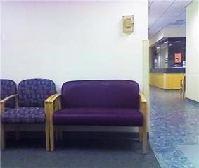 An extra wide chair beside a number of normal sized chairs.