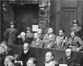 a black and white photograph of a US court room in Nuremberg with several rows of German defendants sitting on a tiered stand with guards standing behind them