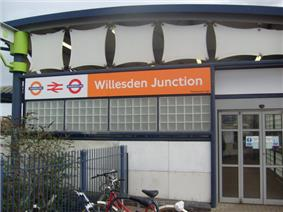 A white-panelled building with a rectangular, orange sign reading