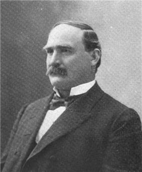 A man with receding, black hair and a thick, black mustache wearing a black jacket and tie and white shirt