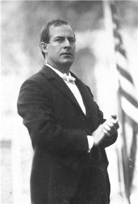 Three-quarters standing portrait of Bryan in a dark suit and white tie, with hands clasped before him, and with a serious and commanding expression