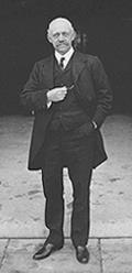 A standing man in three-piece suit, facing camera. He is about 60 and is bald with a mustache. His left hand is in his pants pocket, and his right hand is in front of his chest, holding his pocket watch.