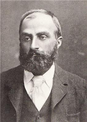 Heavily bearded man with dark receding hair, wearing a dark coloured jacket, white collar and pale tie. He is looking slightly to the left, with a solemn expression