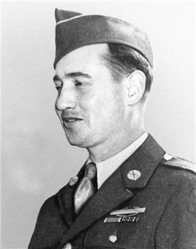 Head and shoulders of a white man wearing a garrison cap tilted over his right ear and a military jacket with a badge and two ribbon bars on the left breast.