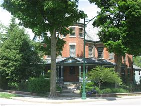 Grand old three-story brick house with porch