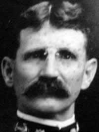 Black-and-white frontal headshot of man with small glasses and a neatly trimmed mustache. The edge of a Navy uniform is around his neck.