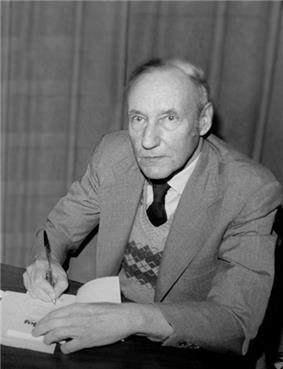 Older man wearing a chequered sweater under a suit coat. He is sitting at a table and signing his autograph in a book, facing the camera.