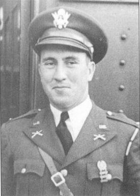 Head and torso of a smirking white man wearing a peaked cap and a military jacket, adorned with pins and badges and a strap running diagonally across his chest, over a shirt and tie.